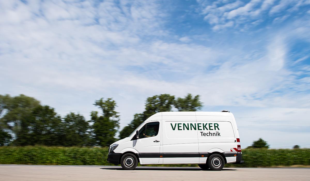 Ein Transporter der Venneker Technik fährt über einen Hof.