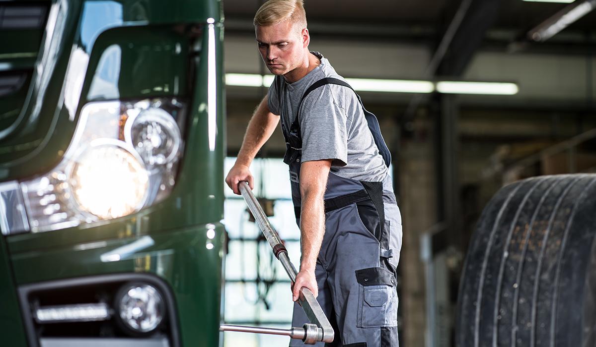 Ein Mitarbeiter wechselt die Reifen eines LKWs der Venneker Gruppe