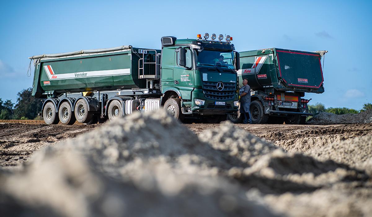 Zwei LKW der Venneker Gruppe stehen in einer Sandkuhle