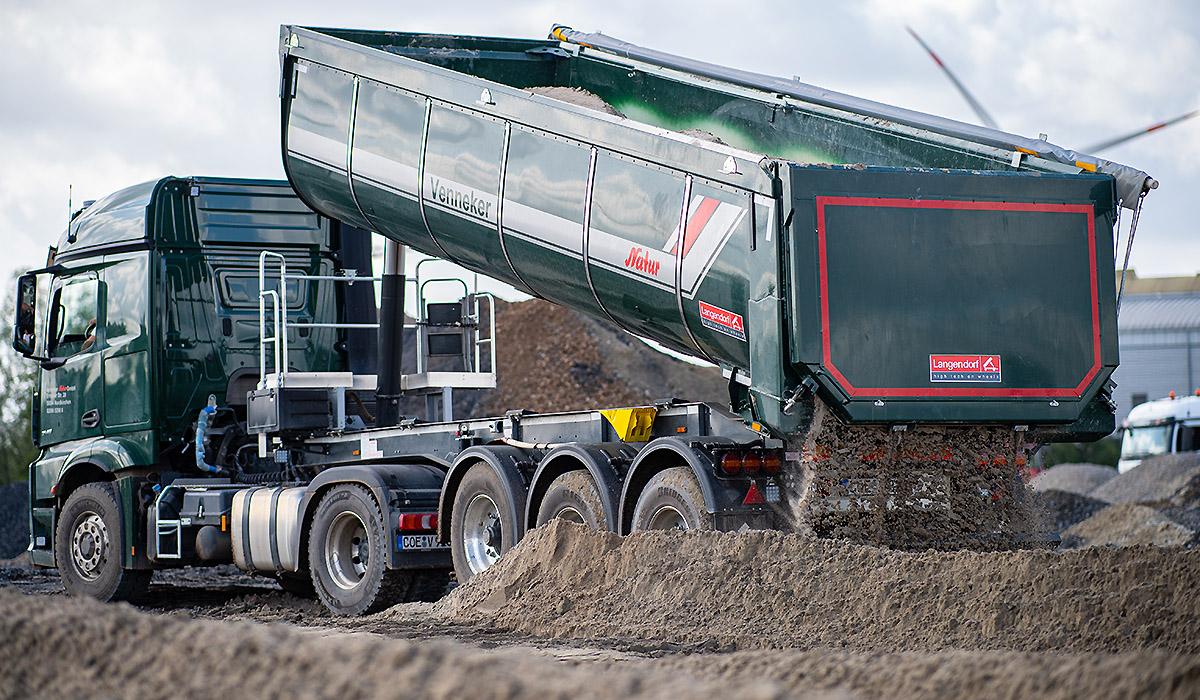 Ein Schüttguttransporter von Venneker Natur lädt Schüttgut ab.