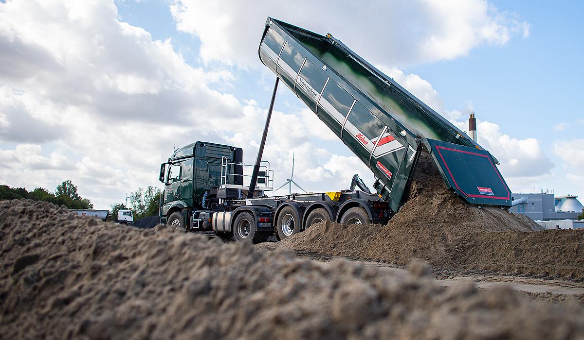 Ein Schüttguttransporter von Venneker Natur lädt Erde ab.