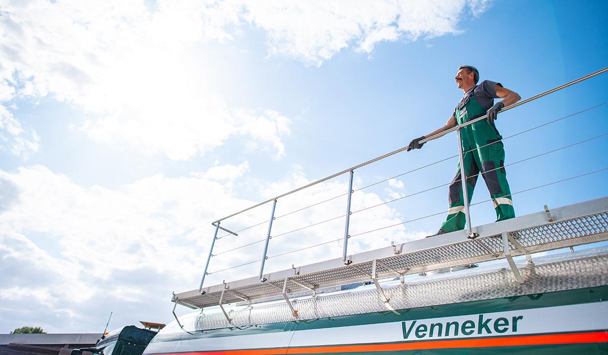 Ein Berufskraftfahrer von Venneker Natur steht auf einem Gülletransporter.