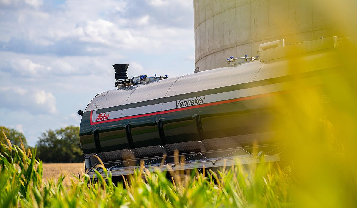 Ein Gülletransporter von Venneker Natur steht vor einem Gülllesilo.