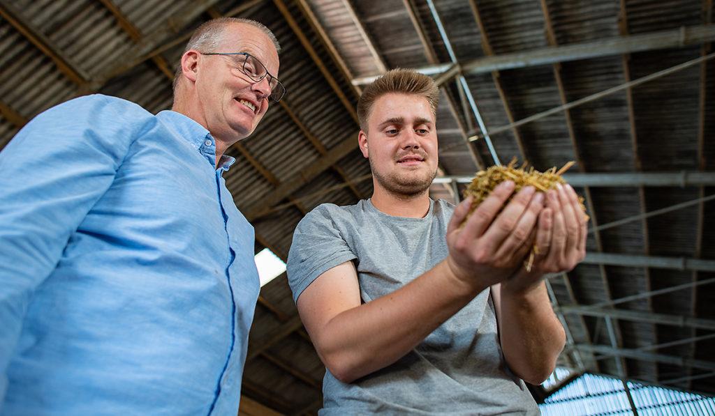 Ein Außendienstmitarbeiter der Venneker Gruppe steht mit einem Landwirt im Stall.