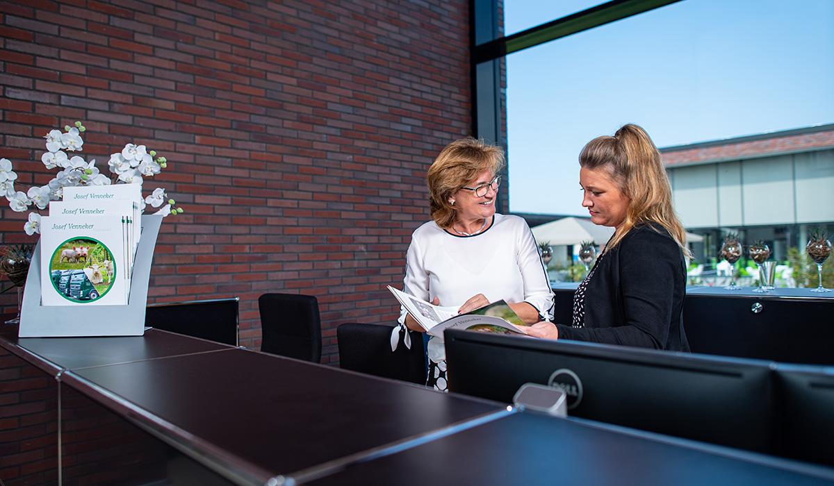 Zwei Mitarbeiterinnen der Venneker Gruppe stehen hinter dem Empfang in der Venneker Zentrale in Nordkirchen.