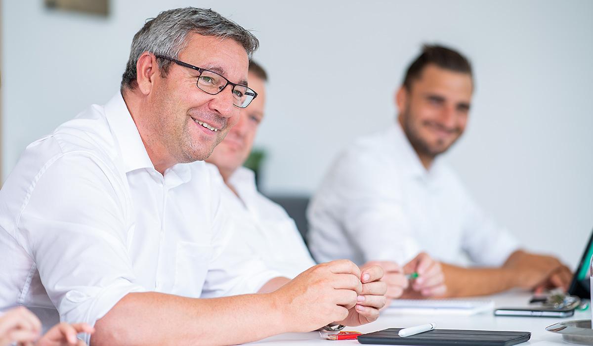 Ein Mitarbeiter sitzt in einer Mitarbeiterbesprechung in der Venneker Zentrale in Nordkirchen.