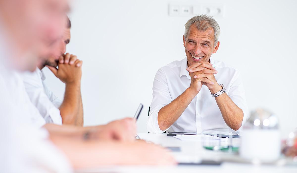 Albert Venneker sitzt mit seinen Mitarbeitern in einer Besprechung in der Venneker Zentrale in Nordkirchen.