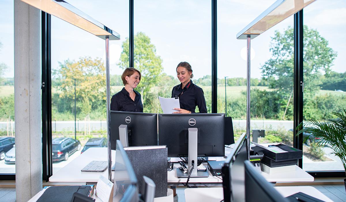Zwei Mitarbeiterinnen aus dem Bereich Viehvermarktung stehen in einem Büro der Venneker Zentrale in Nordkirchen.