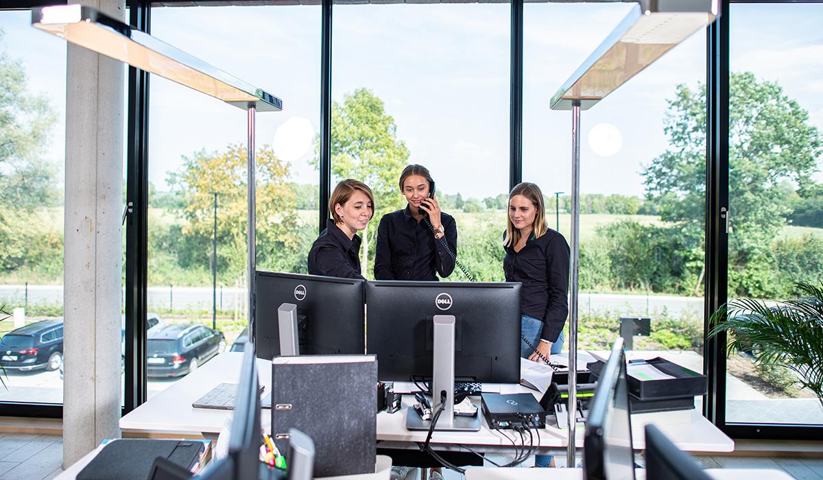 Drei Mitarbeiterinnen aus dem Bereich der Viehvermarktung stehen in einem Büro der Venneker Zentrale in Nordkirchen